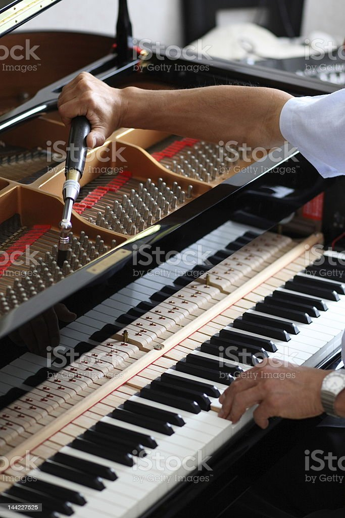 Man working hard to hand tune a piano stock photo