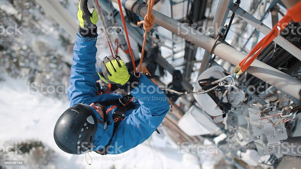 Man working high above the ground on a communication tower stock photo