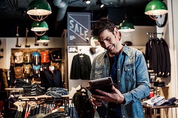 hombre trabajando en un pequeño negocio tienda minorista en de moda - moda de negocios informal fotografías e imágenes de stock