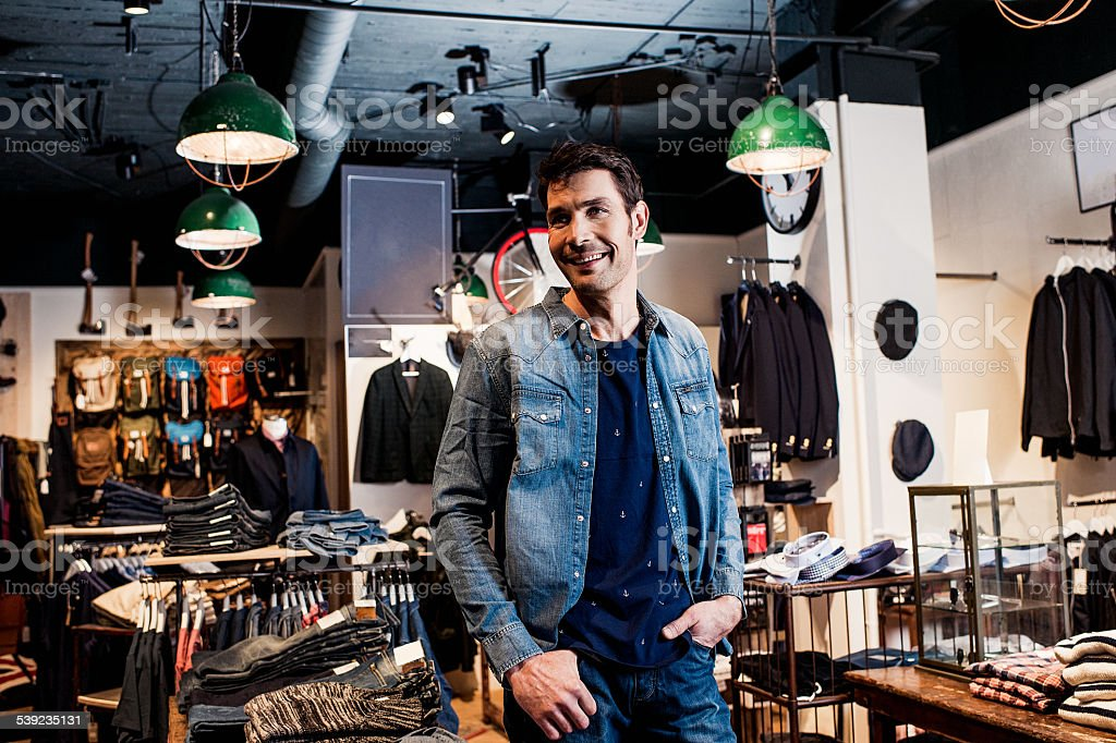 Man working in a small business retailer at fashion store royalty-free stock photo