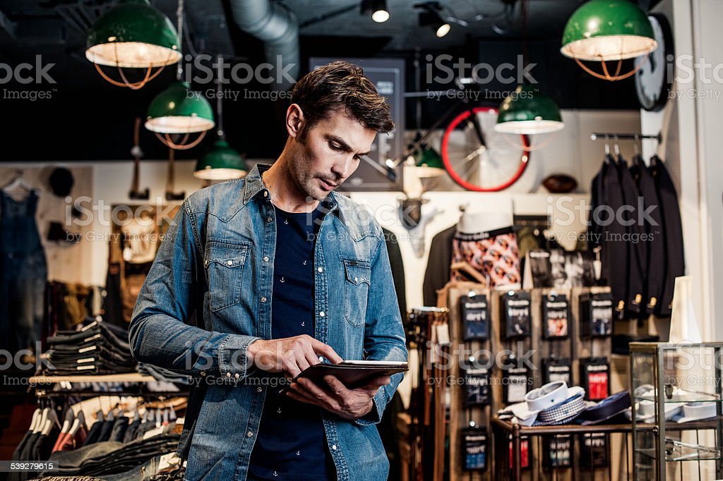Man working in a small business retailer at fashion store stock photo