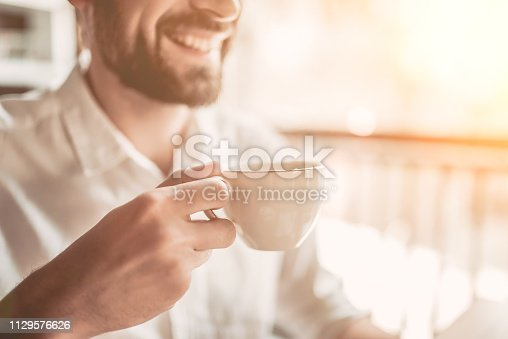 Cropped image of handsome man smiling with cup of coffee in hand.
