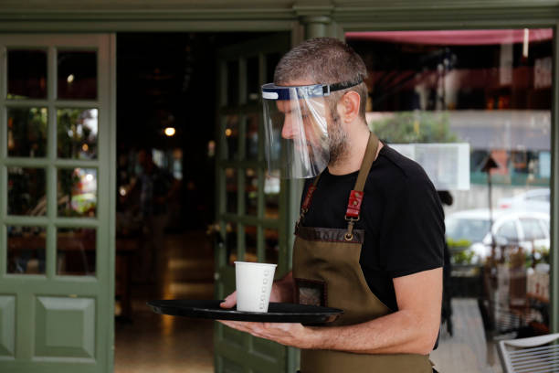Man working in cafe, with face mask stock photo