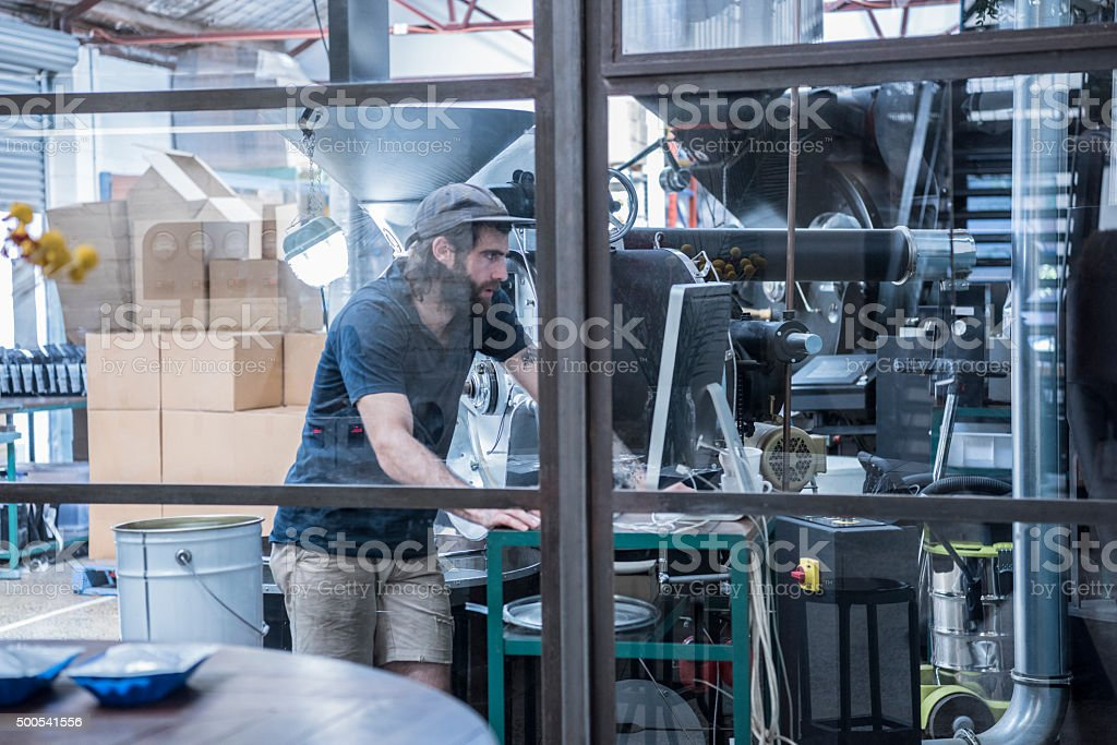 Man working in coffee roasting warehouse, using computer with machinery stock photo