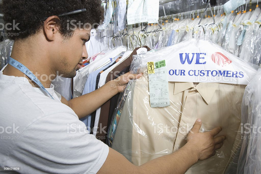 Man working in dry cleaners stock photo