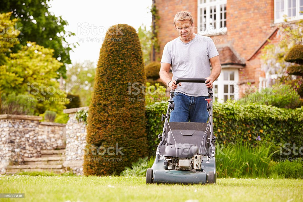 Man Working In Garden Cutting Grass With Lawn Mower stock photo