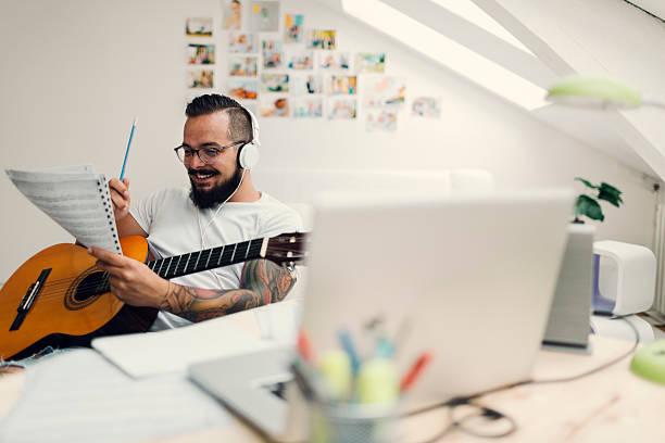mann arbeitet auf seinem zuhause aufnahmestudio. - musiknoten tattoos stock-fotos und bilder