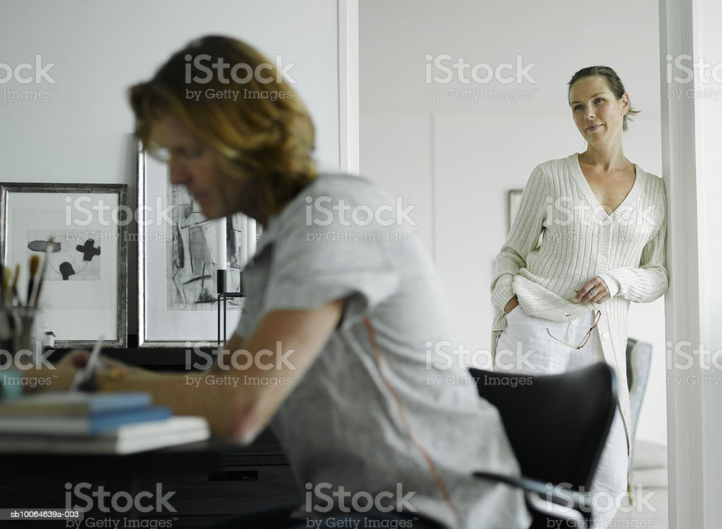 Man working in home office, woman standing in door royalty-free stock photo