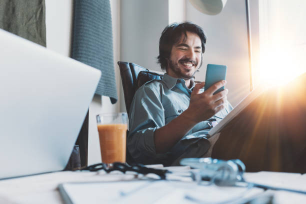 Man working in loft office and using phone stock photo
