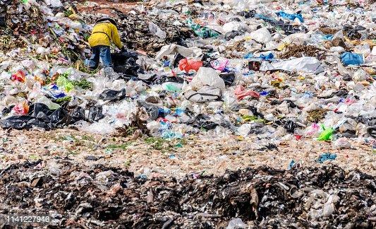 BUENGKHAN PROVINCE, THAILAND - JANUARY 13: Man working in Municipal waste disposal open dump process.  Dump site at Buengkhan Province on JANUARY 13 , 2016 in BUENGKHAN PROVINCE THAILAND