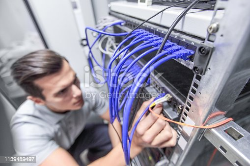Young man working in network server room with fiber optic hub for digital communications and internet