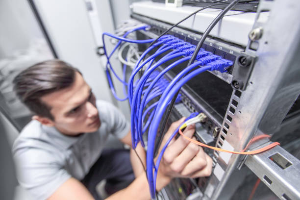 man working in network server room - kabel komputerowy zdjęcia i obrazy z banku zdjęć