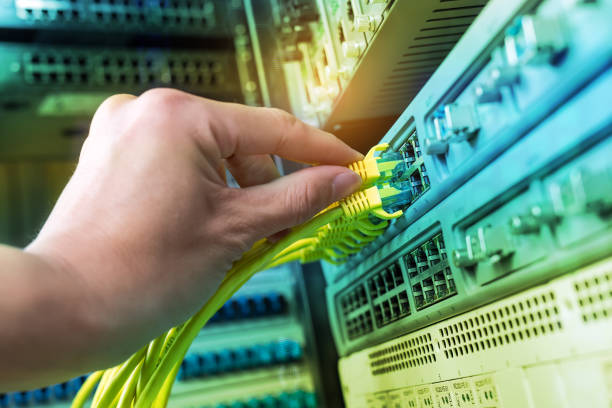 man working in network server room with network hub stock photo