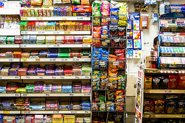Man working in news kiosk, Monument Station, London, UK London, UK - October 15, 2016: a man working in a newsagent kiosk in Monument railway station in central London, UK. He is surrounded by the wares that he is selling, which mainly consists of colourful sweets and candy, and packets of crisps. The man's face is largely obsured, but he is of Indian ethnicity. news stand stock pictures, royalty-free photos & images