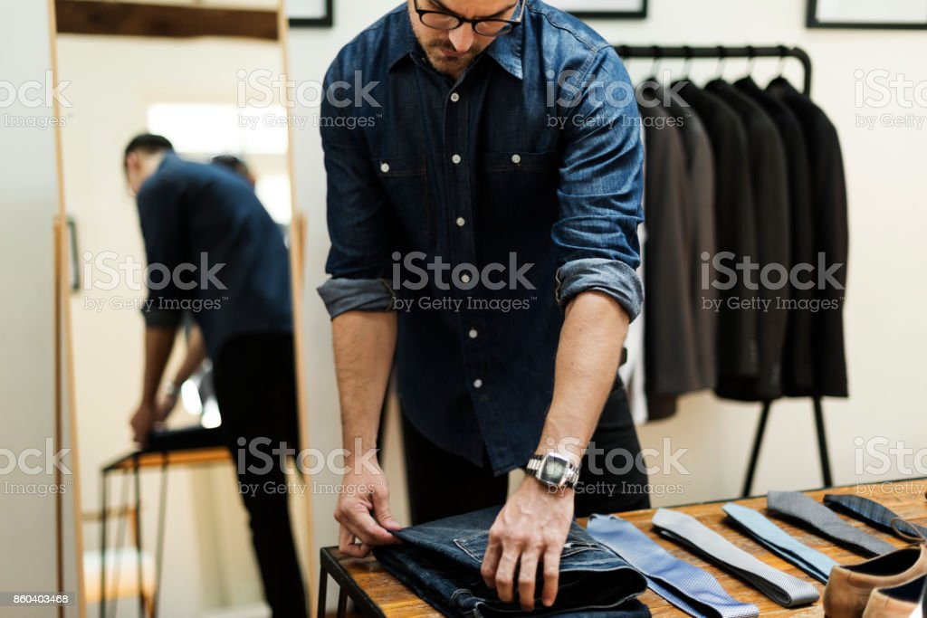 Man working in retail cloth shop stock photo