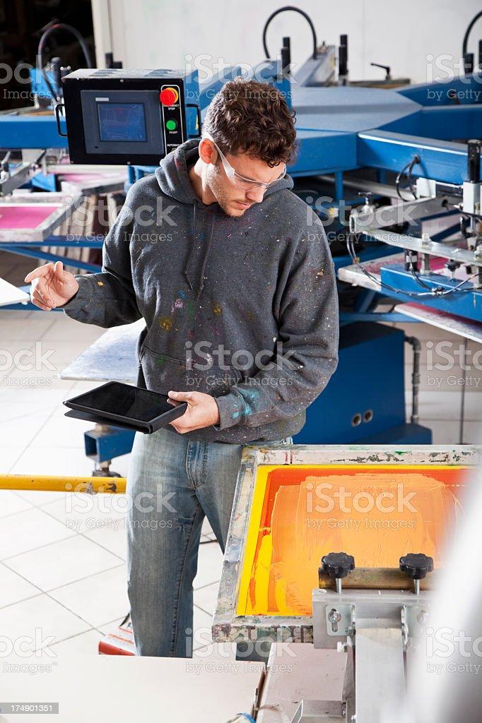 Man working in screen printing shop stock photo