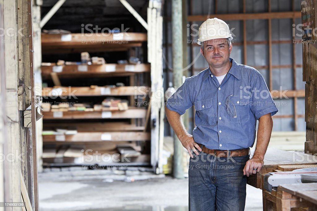 Man working in store selling lumber stock photo