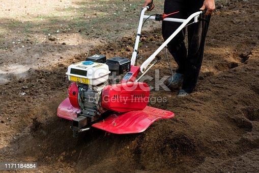 Man working in the garden with garden tiller machine. Garden tiller to work, close up