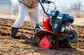 Man working in the garden with Garden Tiller. Garden tiller to work, closeup. Man with tractor cultivating field at spring