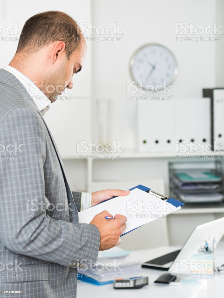 Man working in the office at the laptop with documents royalty-free stock photo