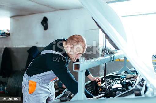 673723668 istock photo Man working on a car 934891882