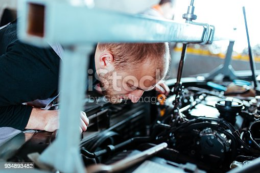 673723668 istock photo Man working on a car 934893482