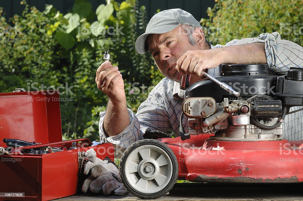 Man working on a lawnmower in the garden. stock photo