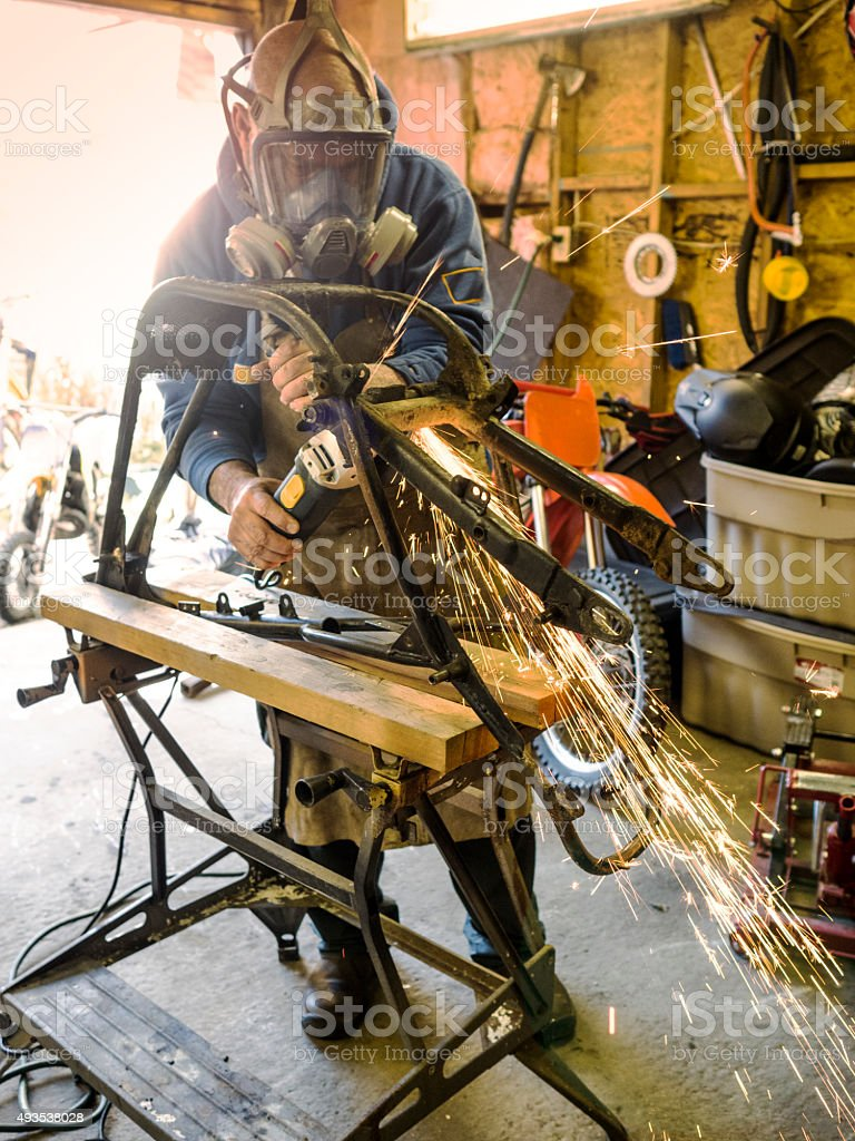 Man working on a motorcycle frame in his garage stock photo