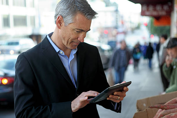 Man working on a tablet in the city on the go stock photo