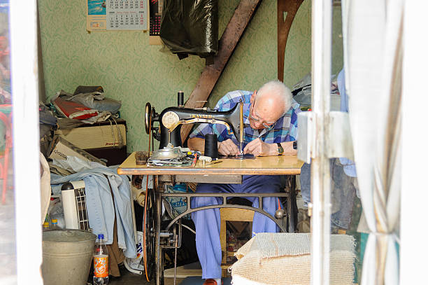 Man working on an old treadle sewing machine stock photo