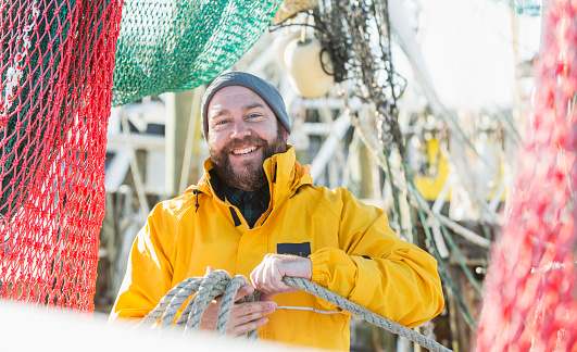 A mature man wearing a raincoat, working on a commercial fishing vessel, a shrimp boat. Fishing nets are hanging down around him.