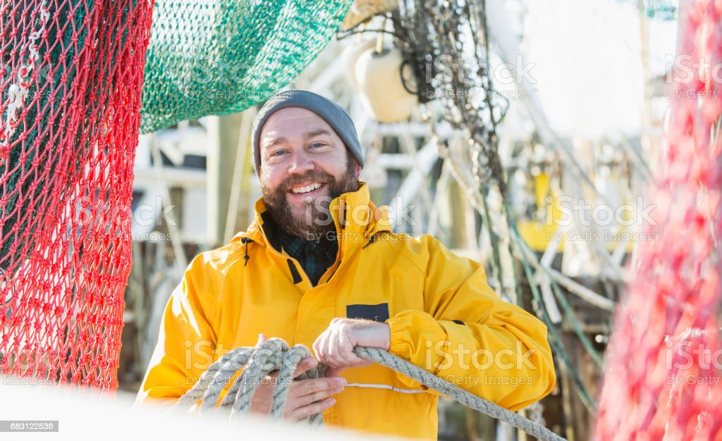 Man working on commercial fishing vessel stock photo