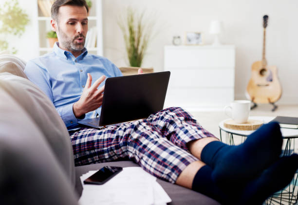 Man working on computer and wearing pajamas stock photo