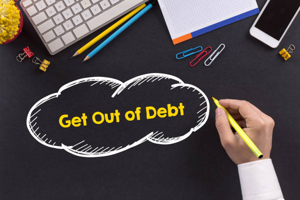 Man working on desk and writing Get Out Of Debt stock photo