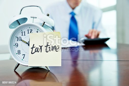 istock Man working on desk with an alarm clock 859196524