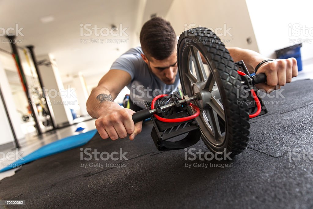 Man working on his abs with a ab roller stock photo