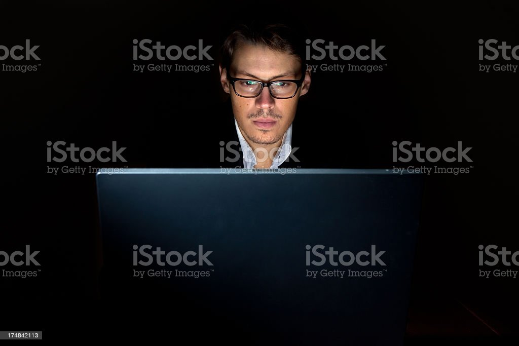 A man working on his laptop late at night stock photo