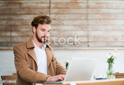 1043434558 istock photo Man working on laptop at cafe 521139443