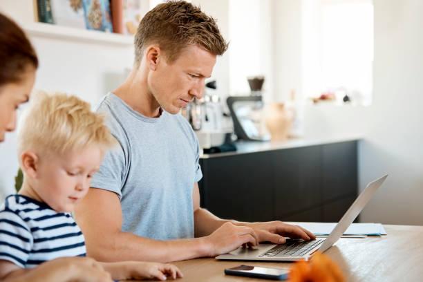 Mann arbeitet auf Laptop von Familie am Tisch – Foto