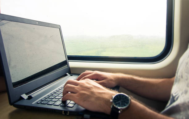 Man working on laptop in a train
