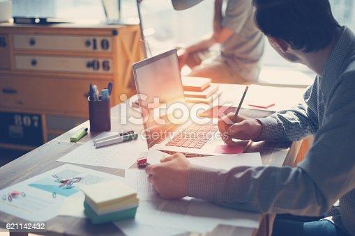 639637280istockphoto Man working on laptop in big open office 621142432
