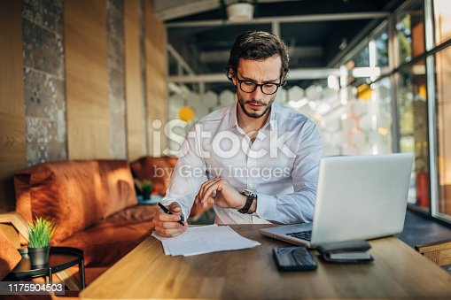 Handsome freelancer businessman working on laptop in cafe