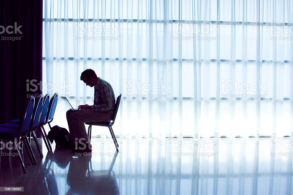 Man working on laptop in convention center room royalty-free stock photo