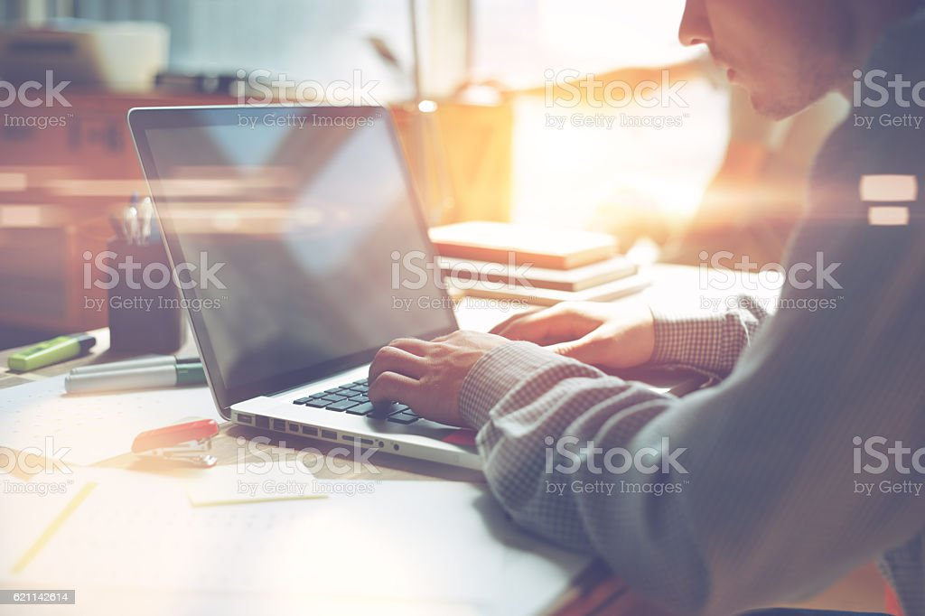 Man working on laptop in office stock photo
