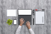 Man working on PC laptop. Office concrete textured desk knolling overhead concept, top close up with laptop, blank tablet, mobile phone, papers, markers, glasses and a plant. blank screen template