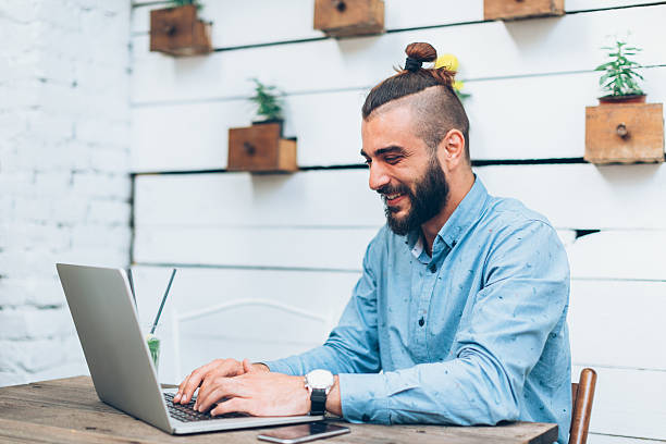 Man working on laptop Young man sitting at cafe and working on laptop man bun stock pictures, royalty-free photos & images