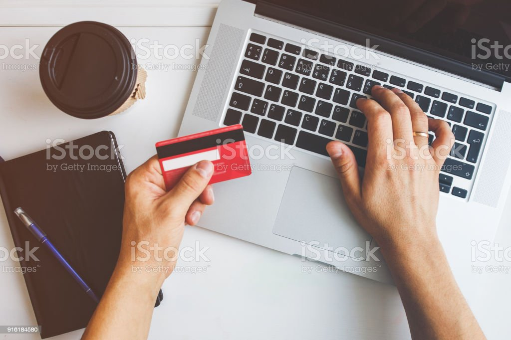 Man working on laptop placed on white desk stock photo