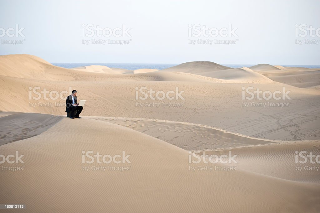 Man working on laptop sitting on a sandy desert hill stock photo