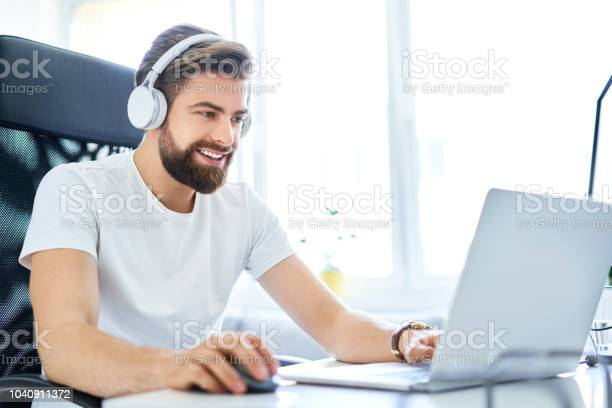 Man working on laptop with headphones from home office student on picture id1040911372?b=1&k=6&m=1040911372&s=612x612&h=kfihm4xz7xb8mszwqhiubimh9wctjhnb0ncabc apzs=