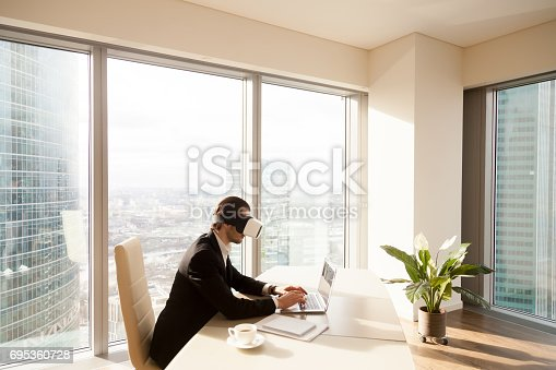 Architect using innovative VR headset for work with 3d visualization. Man at desk working on laptop in virtual reality glasses on head. Modern digital office, augmented and advanced virtual workspace